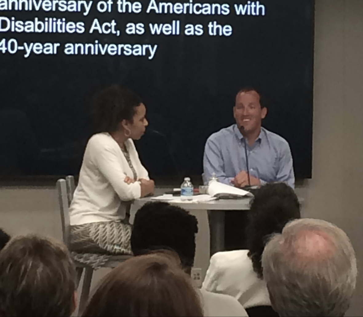 Cynthia and Richard Bernstein sitting at a high top table in front of an audience.